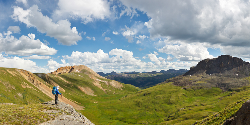 panoramic view of the colorado rocky mountains with hiker in all blue in forefront